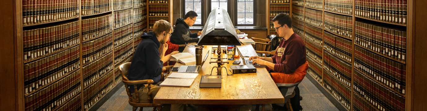 a group of students sitting in a table in a library