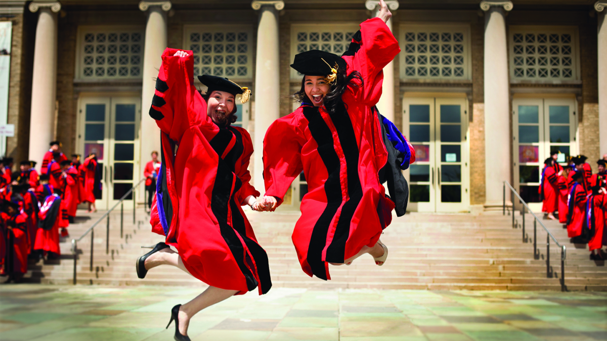 Two students holding hands and jumping in the air, celebrating Convocation
