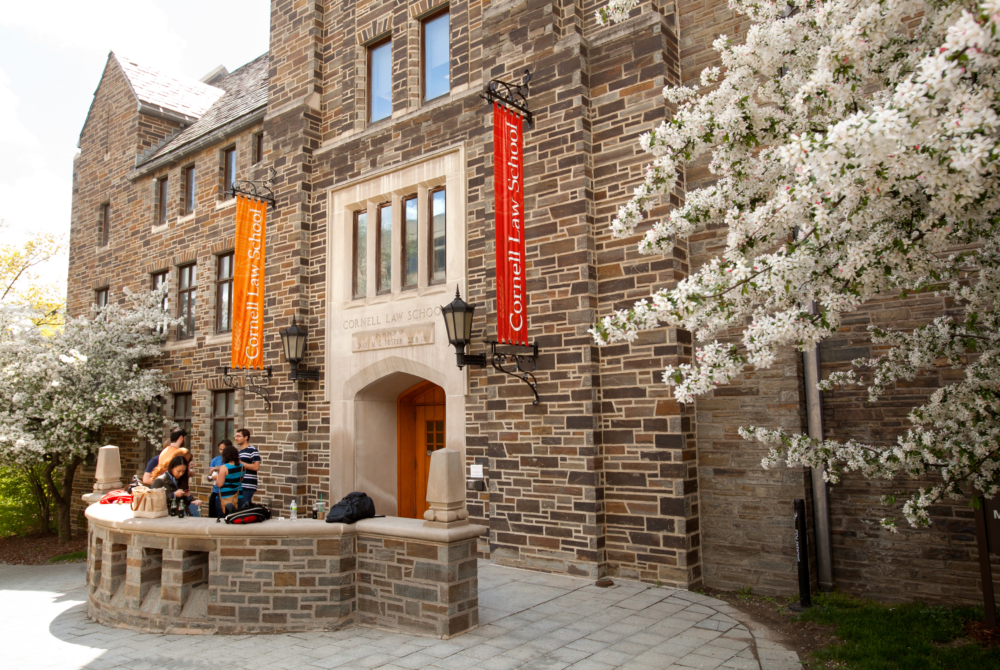 Cornell Law School banners hang on a building in spring
