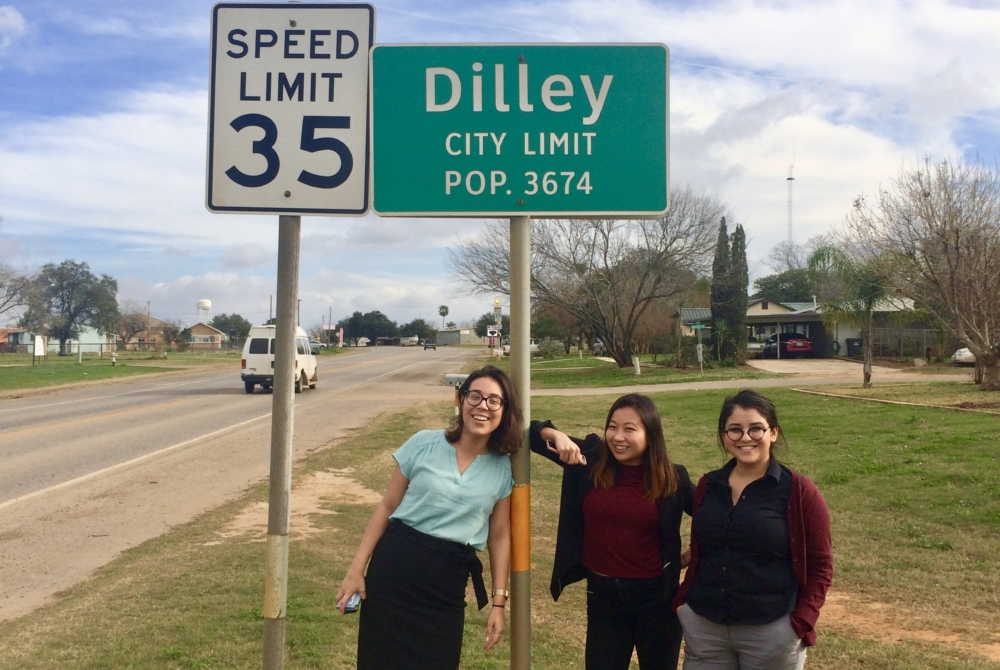 """Three women stand by the side of a road in a rural town. The road sign above their heads reads """"DILLEY CITY LIMIT: POP. 3674"""""""