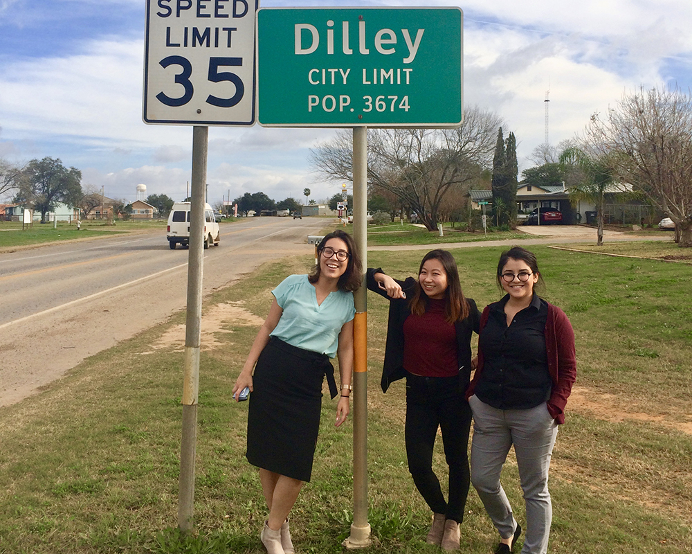 three students with a sign that says Dilley City Limit