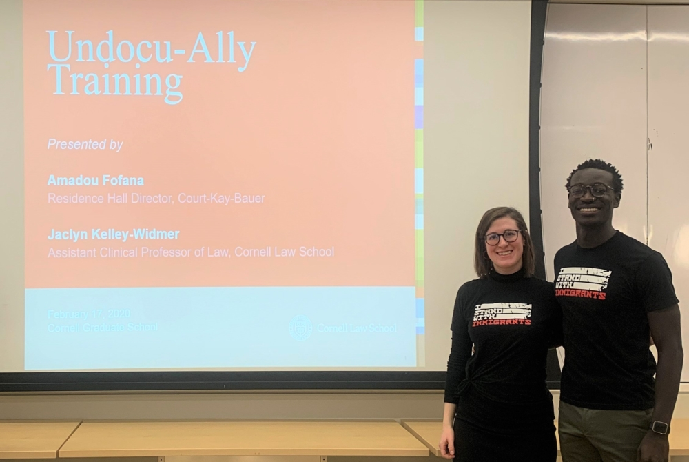 """a man and a woman stand in front of a PowerPoint screen that reads """"Undocu-Ally Training."""""""