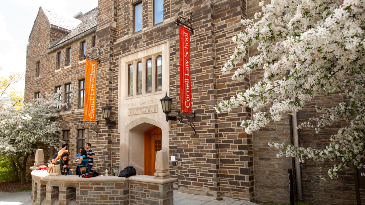 """Students conversion near an entrance to Cornell Law School. Flowering trees are on both sides of the image, and vertical banners displaying """"Cornell Law School"""" flank the building entrance."""