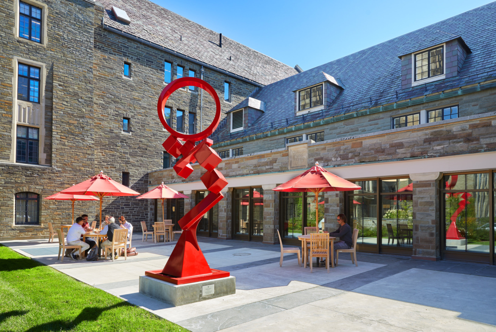 red statues and umbrellas in a courtyard with students eating at tables