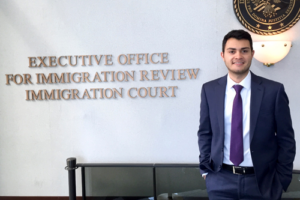 student in front of immigration courtroom sign