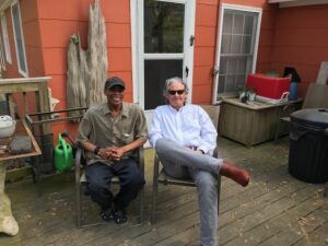 two men sitting on a porch