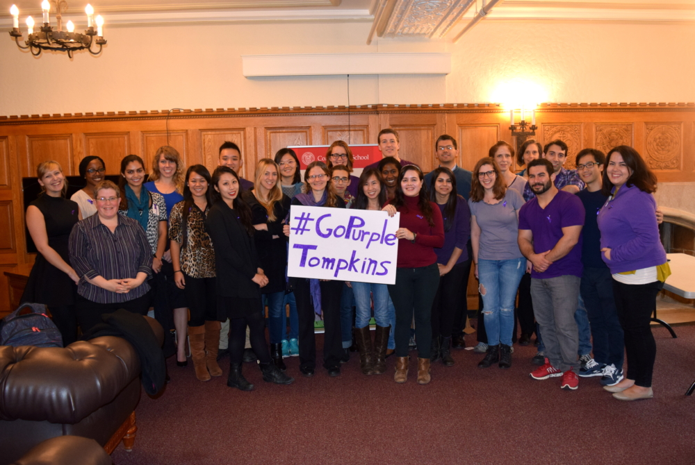 group of people with a sign saying #gopurple Tompkins