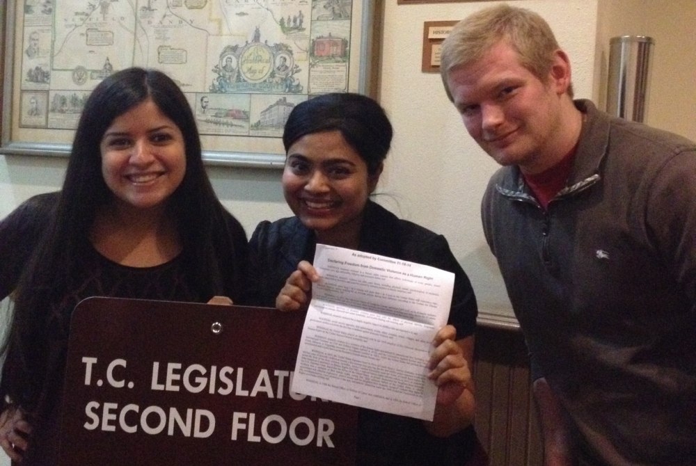 three students with a sign saying TC legislator second floor