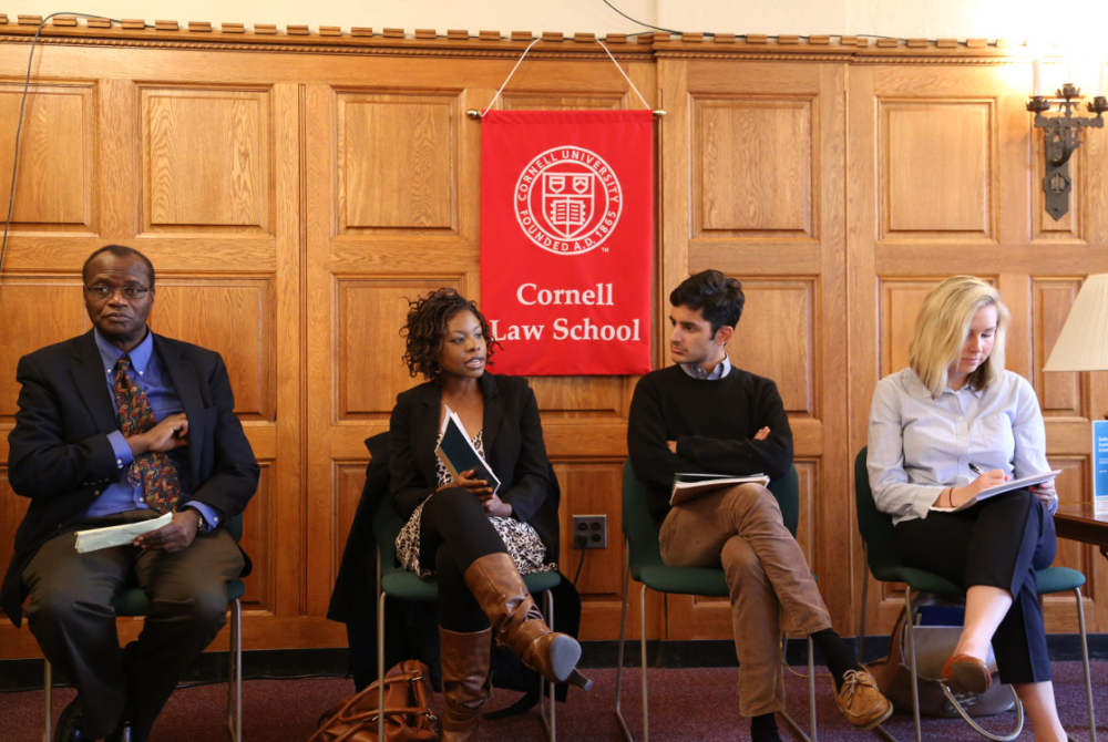 four people, presenting, seated in front of a Cornell Law school flag