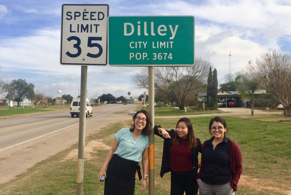 "Three women stand by the side of a road in a rural town. The road sign above their heads reads ""DILLEY CITY LIMIT: POP. 3674"""