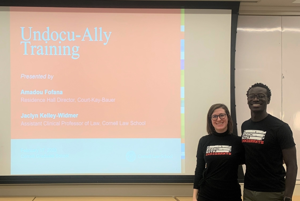 "a man and a woman stand in front of a PowerPoint screen that reads ""Undocu-Ally Training."""
