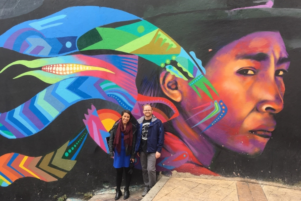 two people in front of a colorful wall mural