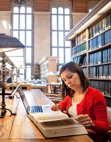 woman in a red shirt reading in a law library