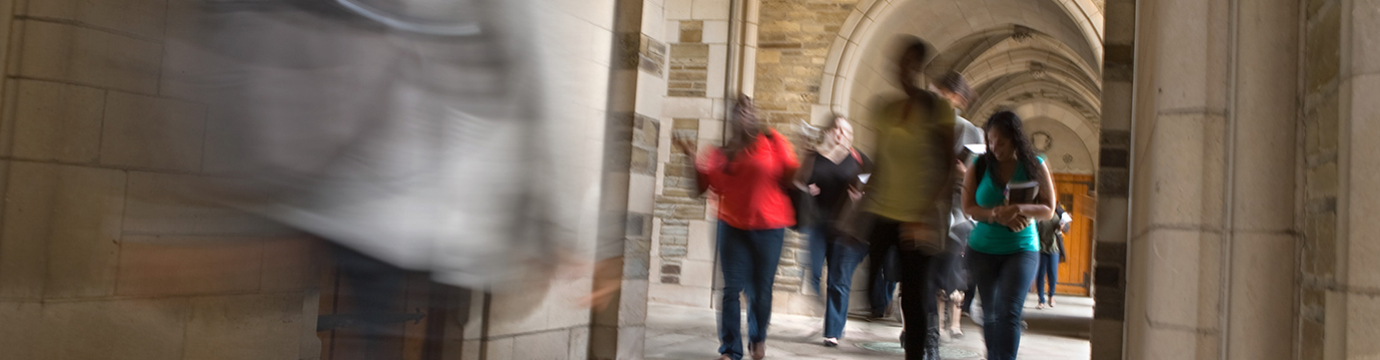 A group of law students walking under archway outside the building