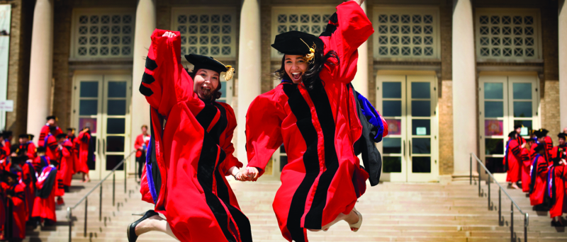 two young women in red graduation attire jump in front of a campus building