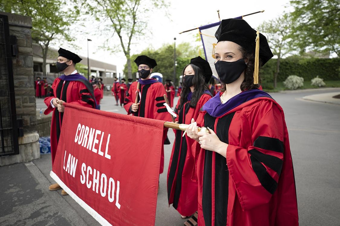 Students in convocation regalia holding Cornell Law School banner