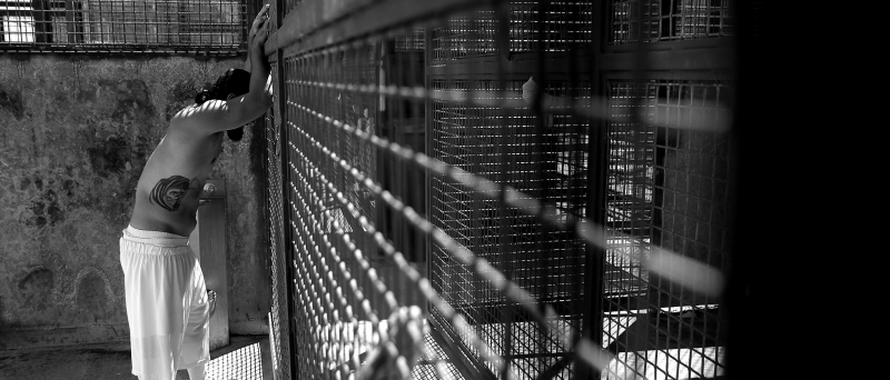 Man leaning against cage/prison bars